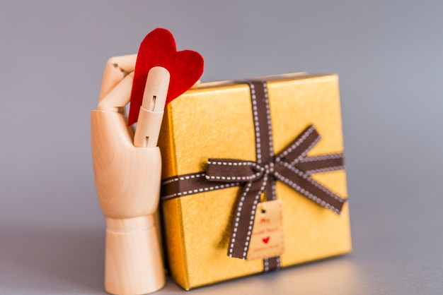 Wooden hand holding red heart near gift box
