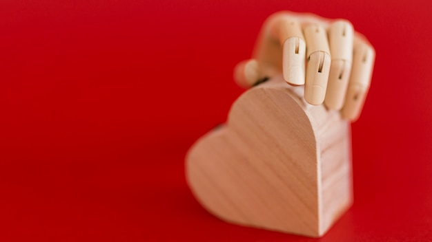 Wooden hand holding wooden heart on red table