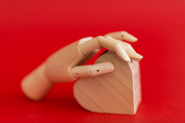 Wooden hand holding wooden heart on table