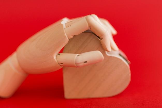 Wooden hand holding wooden heart