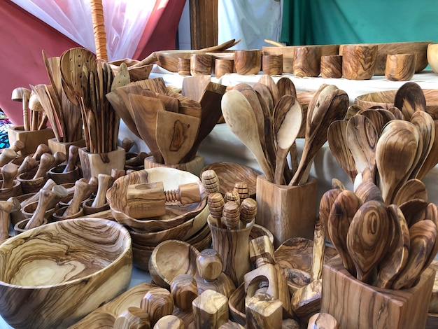 Wooden hand made cutlery and kitchen utensils on market stall outdoors