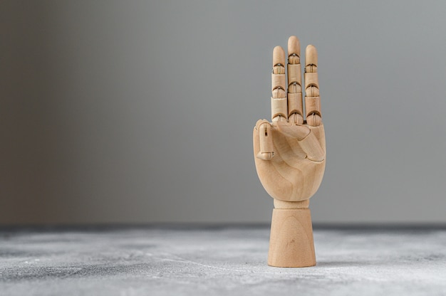 The wooden hand shows three raised fingers. the concept of communication.
