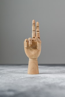 The wooden hand shows two raised fingers. the concept of communication.