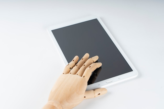 Wooden hand touching a white tablet