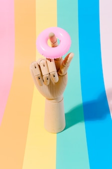 Wooden hand with a float on the finger on a multicoloured background travel and summer 3d
