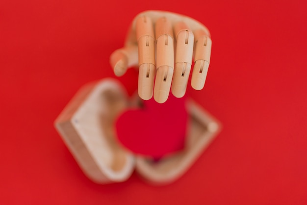 Wooden hand with red heart on table