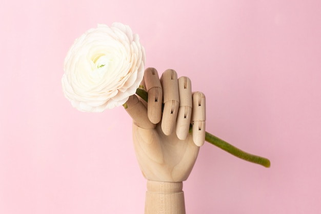 Wooden hand with a white flower on a pink