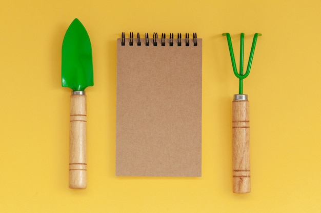 Wooden handled garden hand trowel and hand fork and empty noteboook on yellow background.