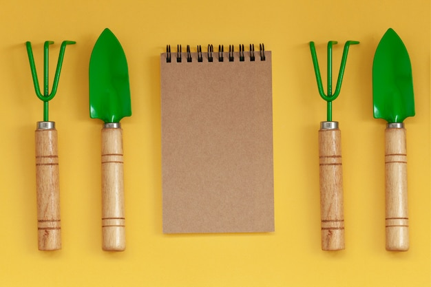 Wooden handled garden hand trowel and hand fork and empty noteboook on yellow background. Premium Photo
