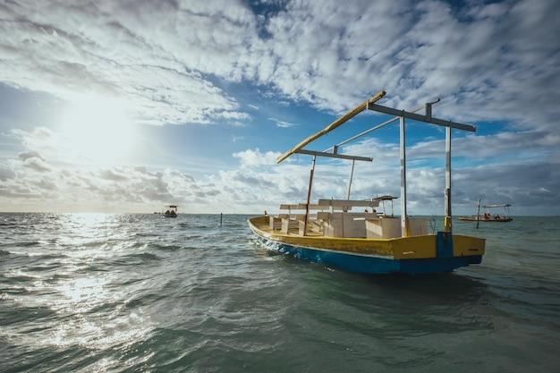 日光と曇り空の下で海に木製の手作りボート