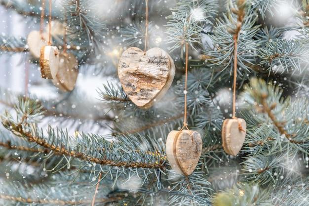 ハートの形をした木製の手作りのクリスマスツリーの装飾は、緑のクリスマスツリーに掛かっています