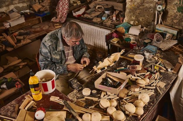 Деревянный парусник ручной работы в столярной мастерской. ремесленник делает деревянный парусник в домашней мастерской