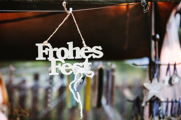 幸せな休日を意味するドイツ語のfrohesfestが付いた木製の吊り下げ式クリスマスデコ