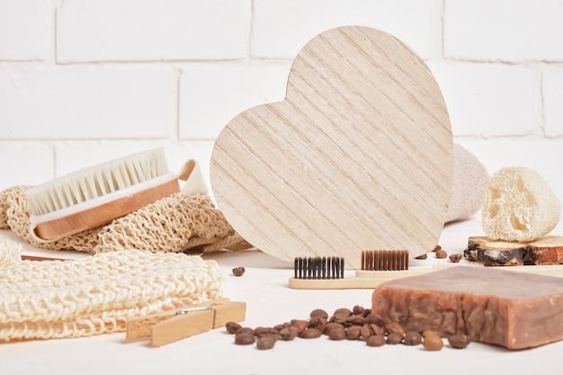 Деревянное сердце и экологически чистые средства гигиены для ухода и гигиены, аксессуары для ванных комнат из натуральных материалов на бежевой поверхности, образ жизни без отходов