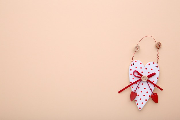 A wooden heart on a beige background.