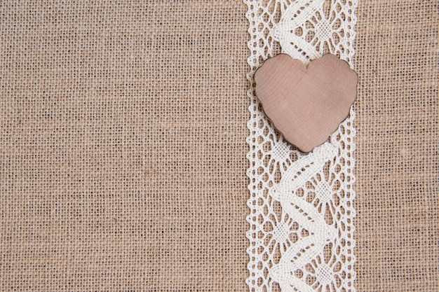 Wooden heart on lace on burlap close up with copy space
