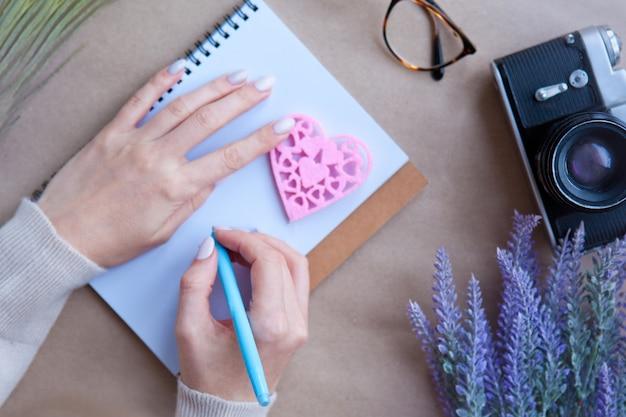 木製のハートloveとテーブルの上のノートとレトロなカメラの後ろに女性の手。手紙を書くコンセプト。ハートの形のシンボル。バレンタイン-ロマンチックな挨拶と手紙のライフスタイルの気持ちの概念