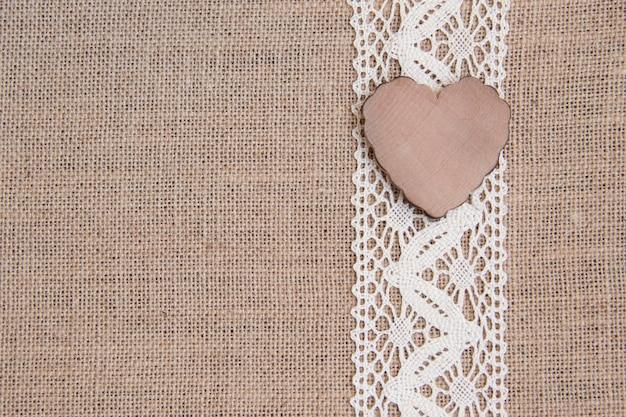 Деревянное сердце на шнурке на мешковине крупным планом с копией пространства