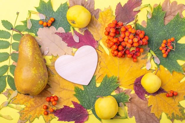 Деревянное сердце на разноцветных красных, оранжевых, зеленых сухих опавших осенних листьях и оранжевых ягодах рябины, яблоках и грушах на желтом фоне. осень - любимое время года