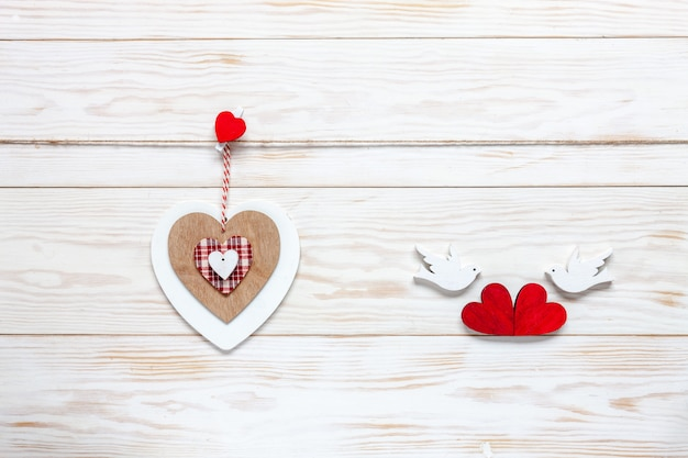 Wooden heart on rope and figurines of pigeons with hearts.