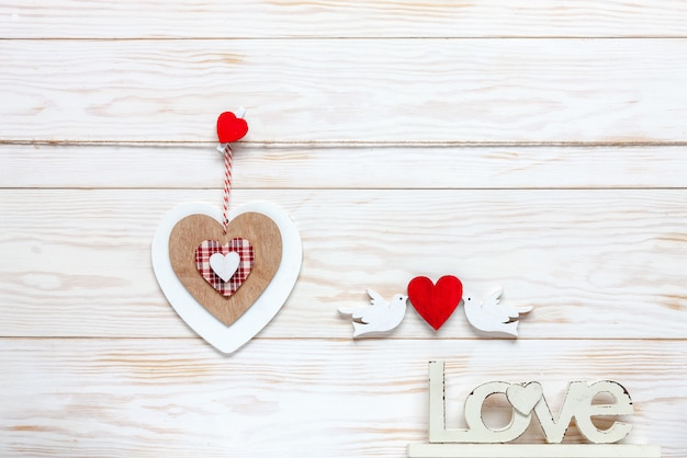 Wooden heart on rope, letters love and figurines of pigeons with hearts.
