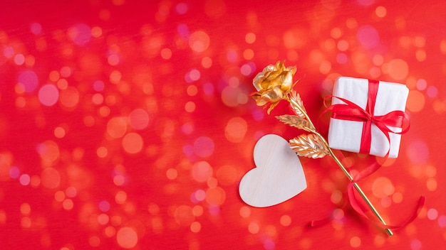 Wooden heart shape, a gift in white paper and a red ribbon and a yellow gold rose symbol of love