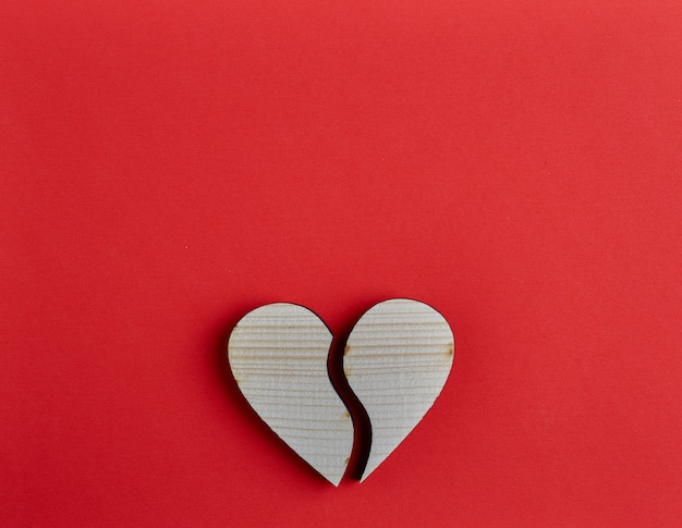 Wooden heart shape on red paper