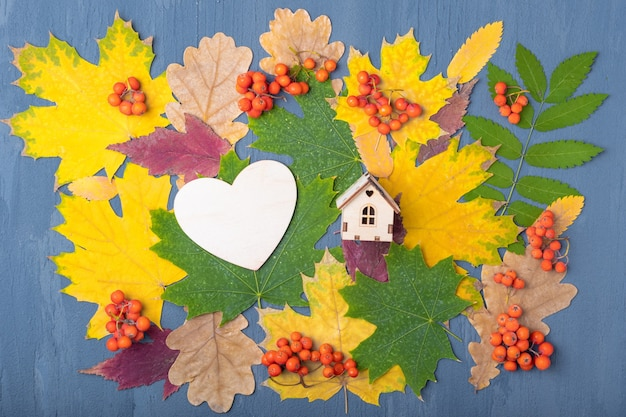 Wooden heart, the shape of a wooden house on multi-colored red, orange, green dry fallen autumn leaves and orange rowan berrie on a blue background. hello autumn concept