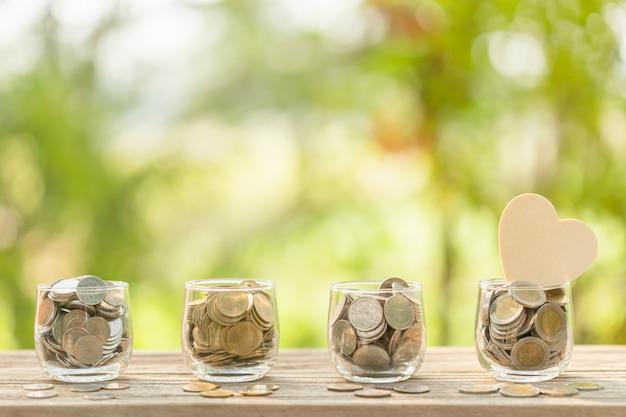 Деревянный символ сердца и монетка в ясном опарнике на деревянном столе. экономия денег для любви или концепции здоровья
