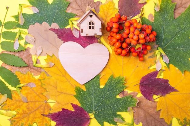 Деревянное сердце, форма деревянного домика на разноцветных красных, оранжевых, зеленых сухих опавших осенних листьях и оранжевых ягодах рябины на желтом фоне. осень - любимое время года