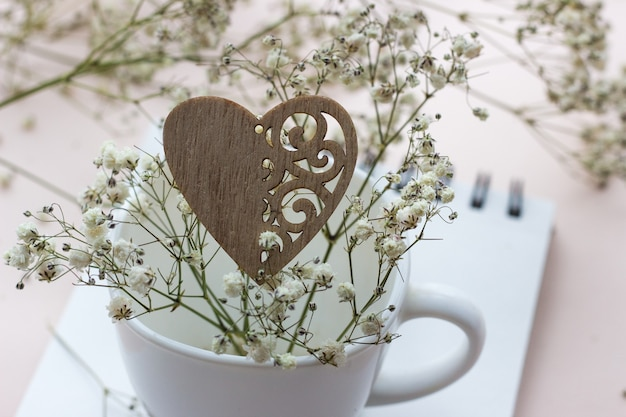 Wooden heart and white porcelain cup with a bouquet of small white flowers on a light background