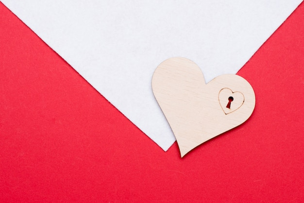 Wooden heart on white and red surface