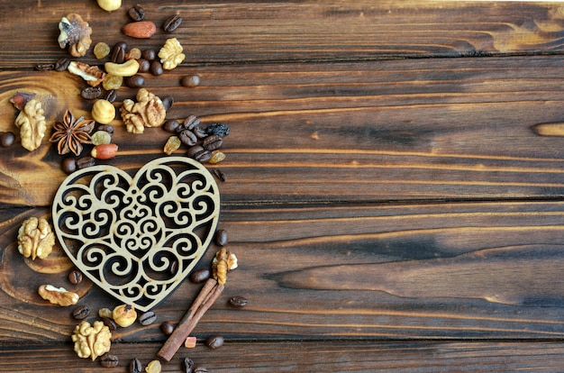 Wooden heart with healthy ingredients raisins, nuts and cinnamon