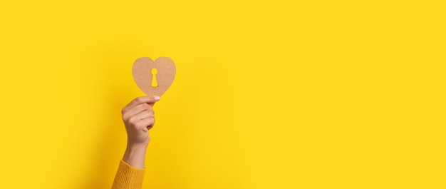 Wooden heart with keyhole in hand over yellow background, panoramic image