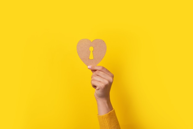 Wooden heart with keyhole in hand over yellow background