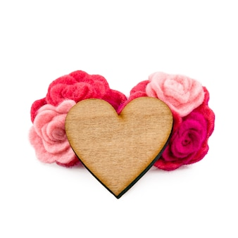 Wooden heart with pink and red wool flowers on white background. valentine's day greeting card.