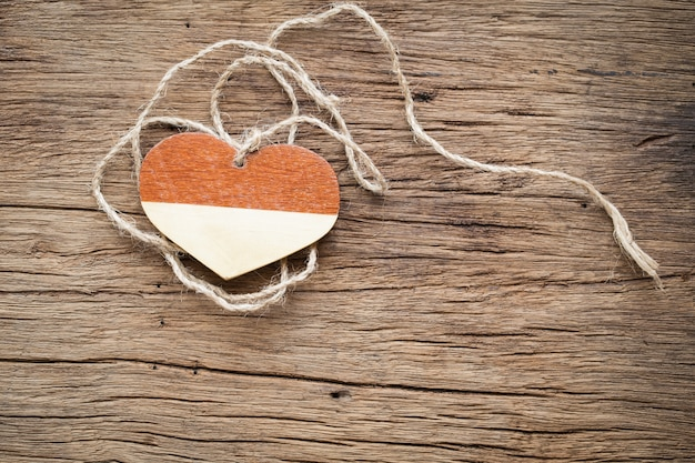 Wooden heart with rope on old wooden