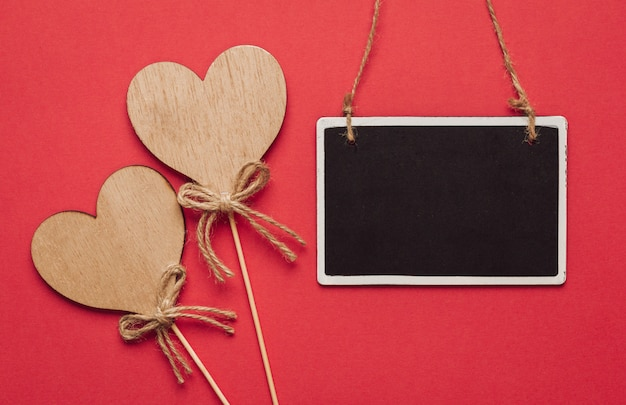 Wooden hearts and a blackboard hanging on a red wall