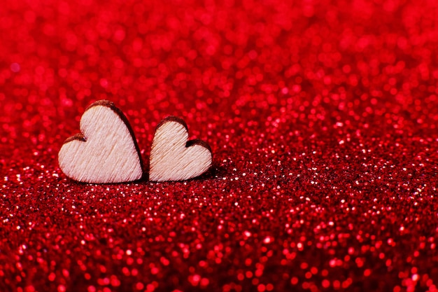 Wooden hearts on brilliant red bright background for a festive decoration
