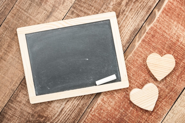 Wooden hearts and chalkboard on wood