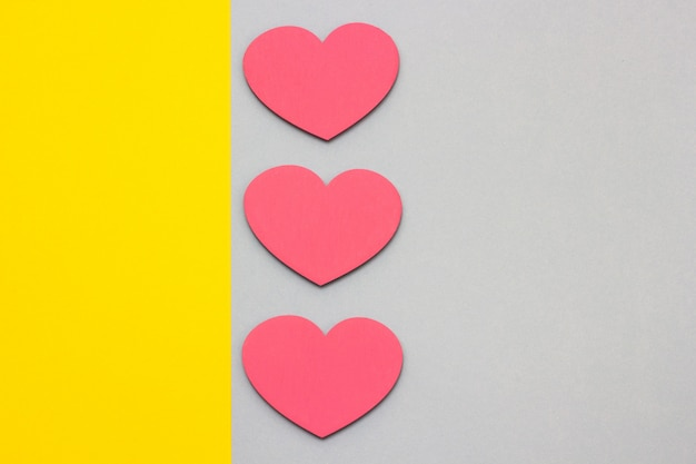 Wooden hearts on a multi-colored background, top view