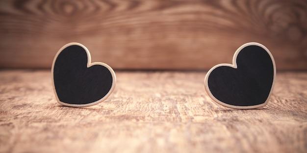Деревянные сердца на деревянном столе.