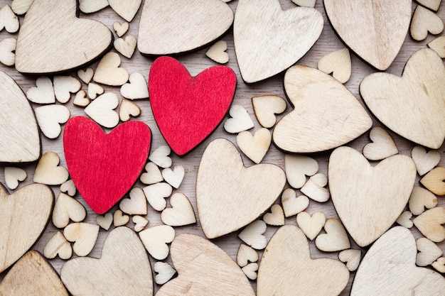 Wooden hearts, one red heart on the heart background.