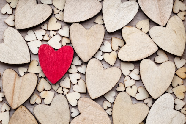 Деревянные сердца, одно красное сердце на сердечном фоне