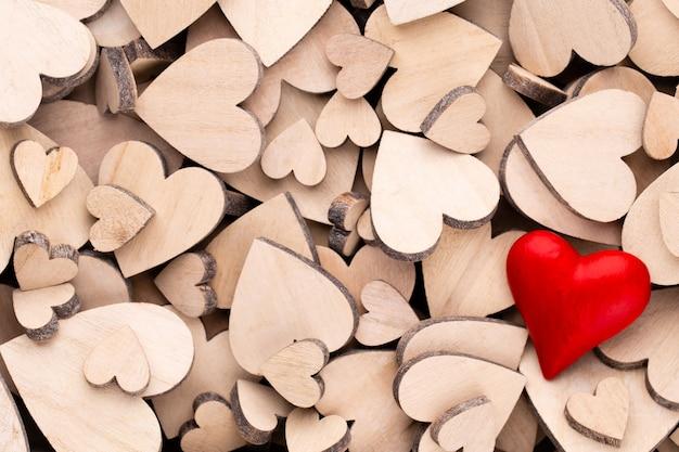Деревянные сердца одно красное сердце на фоне деревянных сердца