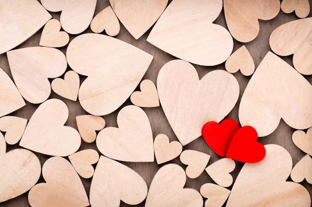 Деревянные сердца, одно красное сердце на фоне деревянного сердца.