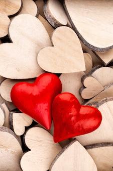 Шаблон деревянные сердца, одно красное сердце на фоне деревянных сердца.