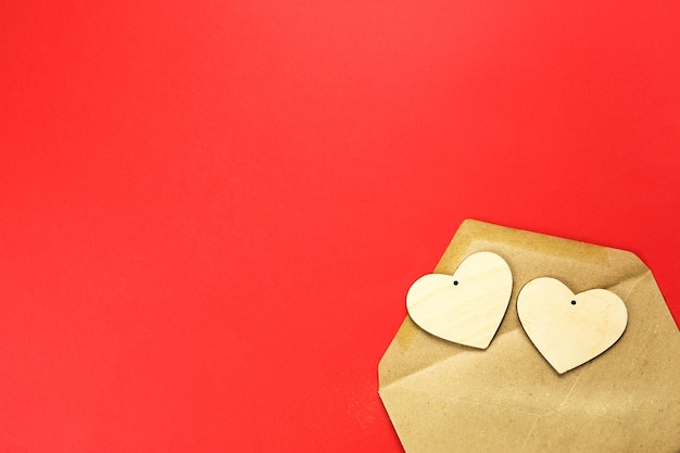Wooden hearts spill out of an open envelope on a red background