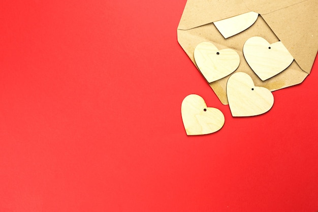 Wooden hearts spill out of an open envelope on a red background.