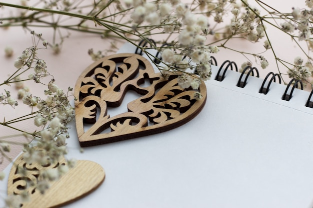 Wooden hearts and white flowers on a light background